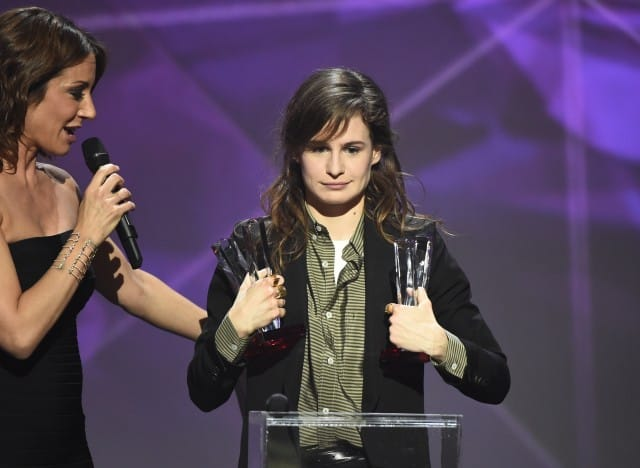 """French singer of the band """"Christine and the Queens"""" Heloise Letissier (R), flanked by French TV host and Master of Ceremony Virginie Guilhaume (L), smiles as she received the best newcomer live show award and the best video clip award during the 31st Victoires de la Musique, the annual French music awards ceremony, on February 12, 2016 at the Zenith concert hall in Paris. AFP PHOTO / BERTRAND GUAY / AFP / BERTRAND GUAY"""