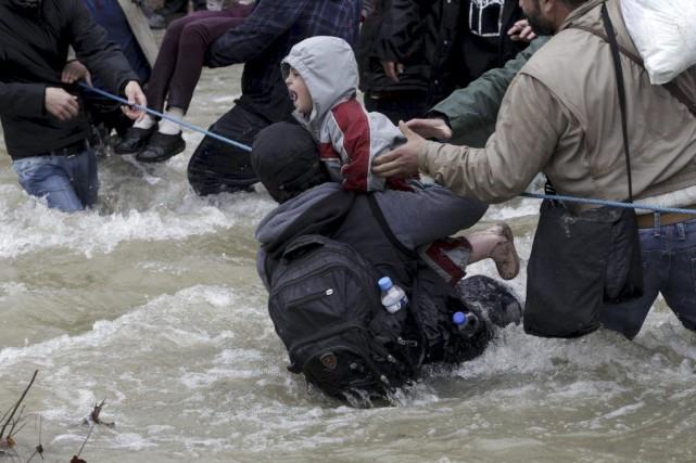 Des migrants ont tenté de traverser une rivière en route vers la Macédoine, près de la frontière avec la Grèce. Photo Reuters