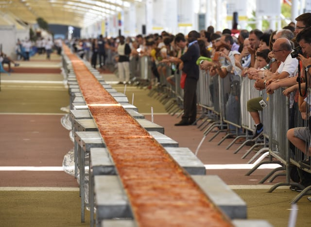 People look at the longest pizza in the world with 1600m long, a new World Guinness Record, on June 20, 2015 in Milan at the Expo Milano 2015. AFP PHOTO / OLIVIER MORIN