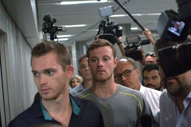 Les nageurs américains Gunnar Bentz et Jack Conger à leur sortie du poste de police à l'aéroport de Rio, jeudi. Photo AP