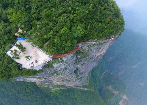 epaselect epa05452645 A picture made available on 03 August 2016 shows an aerial view of tourists walking on a glass-bottomed skywalk on the Panlong (coiling dragon) Cliff on Tianmen Mountain in Zhangjiajie, Hunan Province, China, 01 August 2016. The 100-meter-long walk, giving a clear view of the deep valley behind, is the third glass walkway in the scenic zone. EPA/SHAO YING CHINA OUT