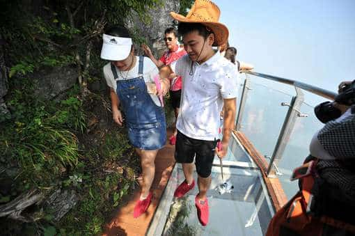 ZHANGJIAJIE, CHINA - AUGUST 01: Tourists walk on the 100-meter-long and 1.6-meter-wide glass skywalk clung the cliff of Tianmen Mountain (or Tianmenshan Mountain) in Zhangjiajie National Forest Park on August 1, 2016 in Zhangjiajie, Hunan Province of China. The Coiling Dragon Cliff skywalk, featuring a total of 99 road turns, layers after another, is the third glass skywalk on the Tianmen Mountain (or Tianmenshan Mountain). (Photo by VCG/VCG via Getty Images)