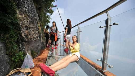 epa05452647 A picture made available on 03 August 2016 shows tourists taking selfies on a glass-bottomed skywalk on the Panlong (coiling dragon) Cliff on Tianmen Mountain in Zhangjiajie, Hunan Province, China, 01 August 2016. The 100-meter-long walk, giving a clear view of the deep valley behind, is the third glass walkway in the scenic zone.  EPA/SHAO YING CHINA OUT