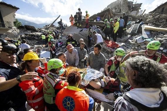 Des secouristes évacuent une femme blessée à Amatrice, où plusieurs corps ont été retirés des décombres. Photo AP
